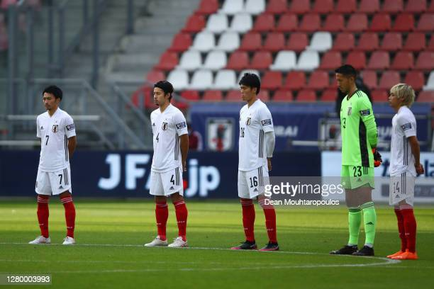 Players stand for a minute's silence in honour of Covid-19 victims ahead of the international friendly match between Japan and Ivory Coast at Stadion...