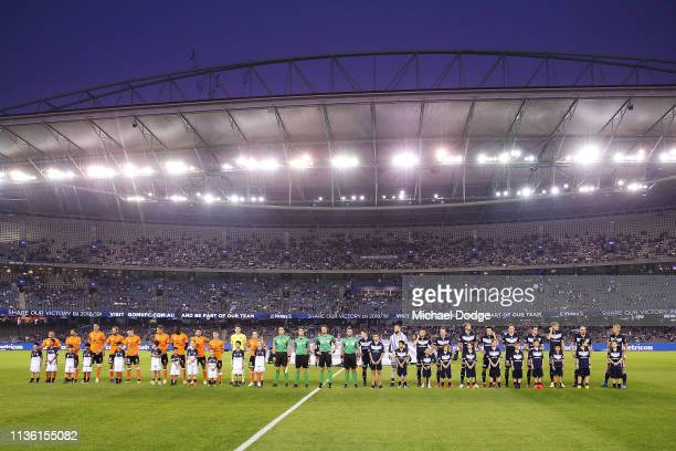 Players stand for a minutes silence in tribute to the Christchuch Mosque terror attack during the ALeague Rd 22 match between Melbourne Victory and...