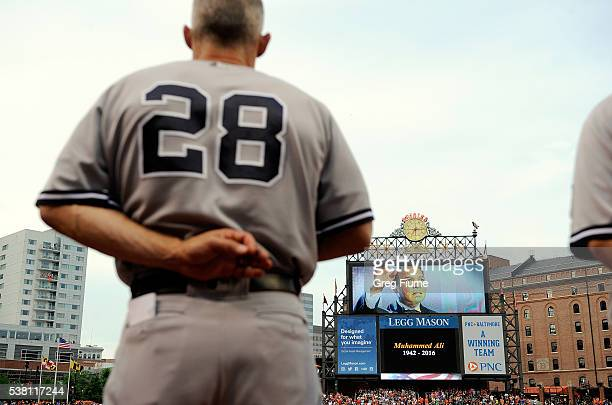 Players stand for a moment of silence for Muhammad Ali before the game between the Baltimore Orioles and the New York Yankees at Oriole Park at...