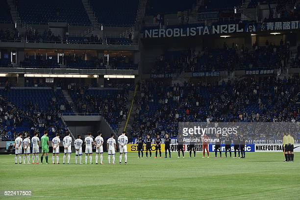 Players stand for a moment of silence for the victims of series of earthquakes in Kumamoto prior to the AFC Champions League Group G match between...