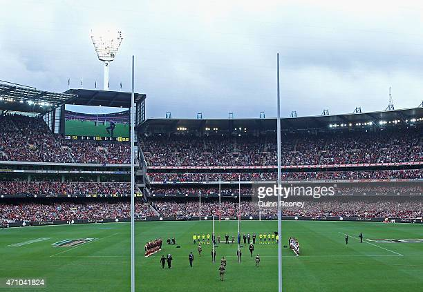 Players stand for the Anzac day Ceremony during the round four AFL match between the Essendon Bombers and the Collingwood Magpies at Melbourne...