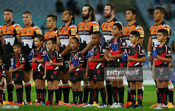Players stand for the national anthems during the round eight NRL match between the Canterbury Bulldogs and the Wests Tigers at ANZ Stadium on April...