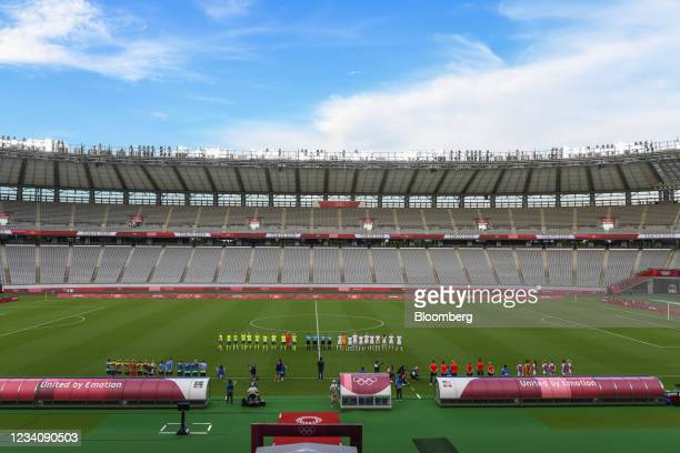 Players stand for their national anthems ahead of an opening round women's football match between the U.S. And Sweden at the Tokyo 2020 Olympic Games...