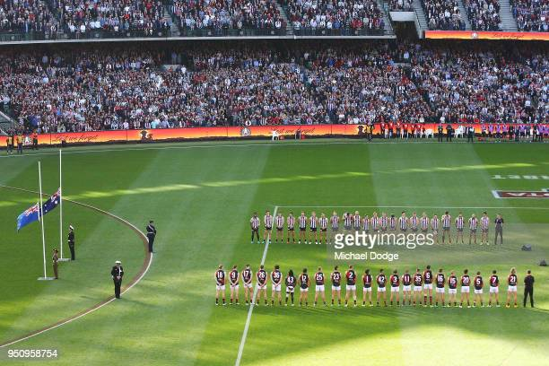 Players stand in line for a minutes silence during the ANZAC observance Players break through the banner together during the round five AFL match...