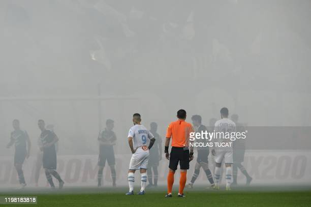 Players stand in smoke from flares lit by Bordeaux's fans during the French L1 football match between Girondins de Bordeaux and Olympique de...