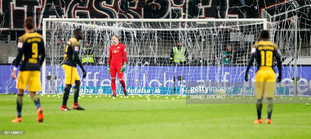 Players stand on the pitch as fans throw tennis balls on the pitch to protest against football games scheduled on Mondays (Montagsspiele) during the German First division Bundesliga football match Eintracht Frankfurt vs RB Leipzig in Frankfurt, Germany, on February 19, 2018. / AFP PHOTO / Daniel ROLAND