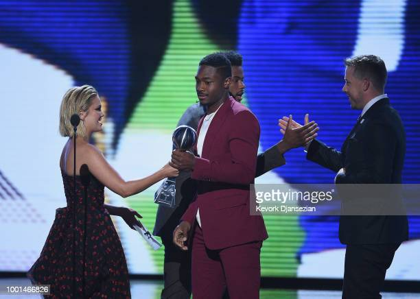NFL players Stefon Diggs and Case Keenum accept the award for Best Moment from actor Olivia Holt and singer Trevor Jackson onstage at The 2018 ESPYS...