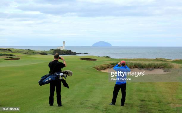 Players stop to take pictures view looking down the par 5 eighth hole with the Turnberry Lighthouse and the island of Ailsa Craig in teh distance on...