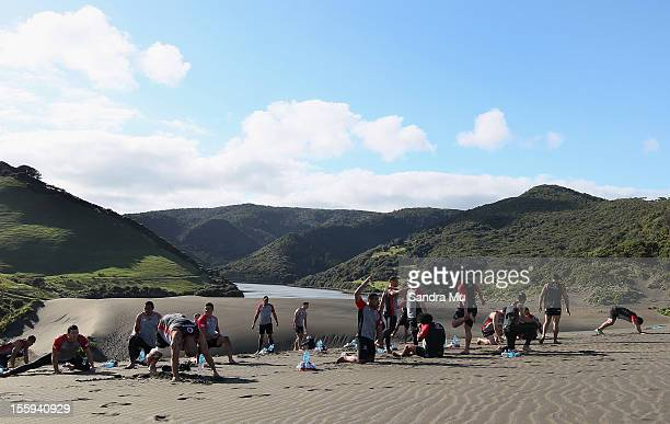 Players stretch on the sand dunes during the New Zealand Warriors NRL training session at Bethells Beach on November 10 2012 in Auckland New Zealand...