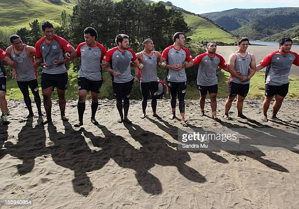 Players support each other as they train on the sand dunes during the New Zealand Warriors NRL training session at Bethells Beach on November 10 2012...