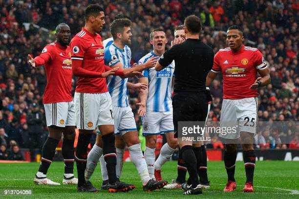 Players surround referee Stuart Attwell as they react after Manchester United's English midfielder Scott McTominay was injured in a collision...