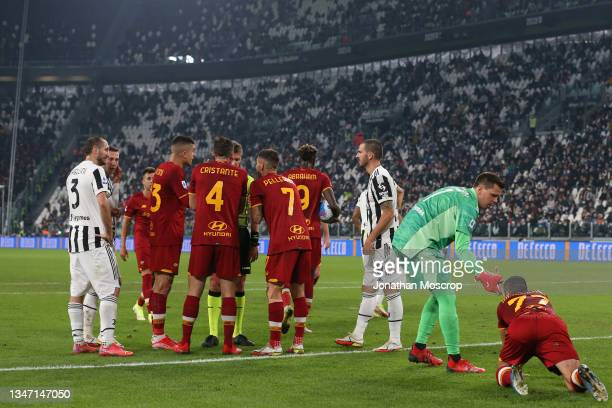 Players surround the referee Daniele Orsato as Wojciech Szczesny of Juventus helps Henrikh Mkhitaryan of AS Roma back to his feet after upending him...