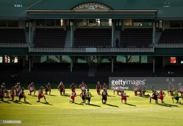 Players take a knee before the round 2 AFL match between the Sydney Swans and the Essendon Bombers at Sydney Cricket Ground on June 14, 2020 in...