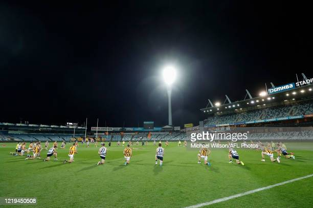 Players take a knee in support of the Black Lives Matter movement before the 2020 AFL Round 02 match between the Geelong Cats and the Hawthorn Hawks...