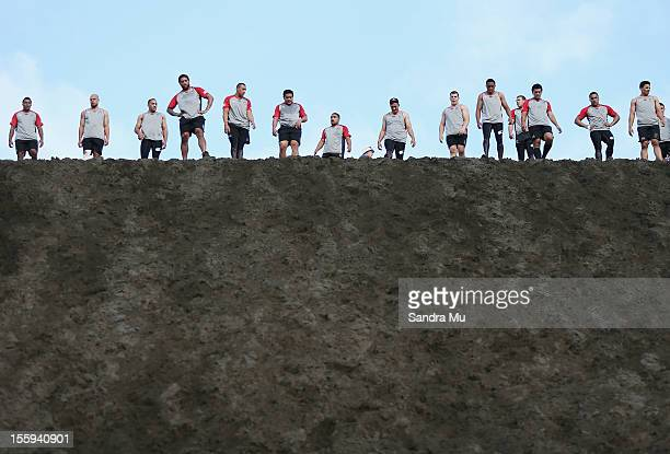 Players take a rest as they train on the sand dunes during the New Zealand Warriors NRL training session at Bethells Beach on November 10 2012 in...