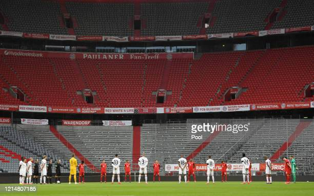 Players take part in a minute of silence to commemorate the Corona pandemic victims prior to the Bundesliga match between FC Bayern Muenchen and...