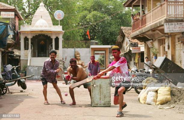 Players take part in a street cricket match during the Holi Fesitval of Colours in the Parel area of Mumbai India 15th March 2006