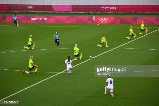 Players take the knee ahead of an opening round women's football match between the U.S. And Sweden at the Tokyo 2020 Olympic Games in Tokyo, Japan,...
