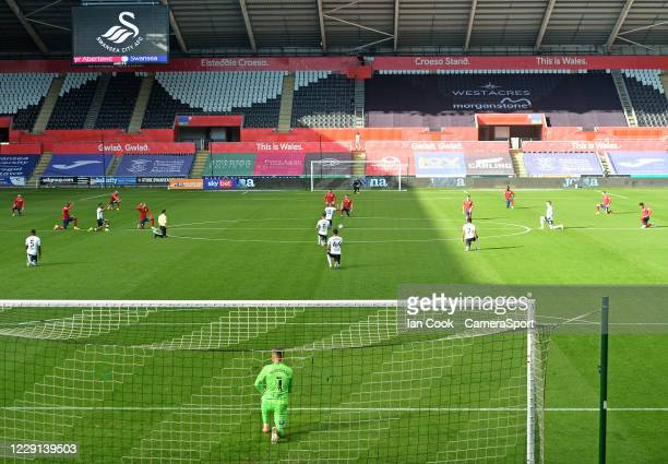 Players take to the knee in the Black Lives Matter movement during the Sky Bet Championship match between Swansea City and Huddersfield Town at...