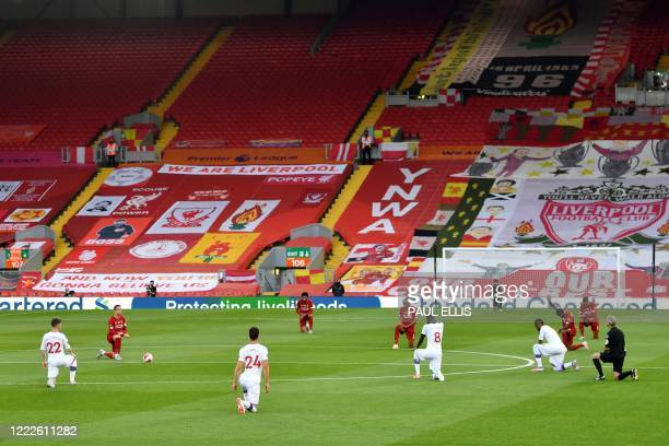 TOPSHOT Players thak the knee before kick off during the English Premier League football match between Liverpool and Crystal Palace at Anfield in...