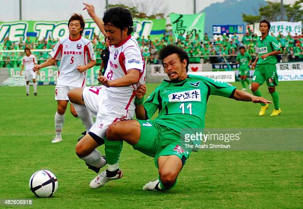 Players tussle for the ball during the JFL match between Gainare Tottori and Arte Takasaki at Torigin Bird Stadium on October 3 2010 in Tottori Japan