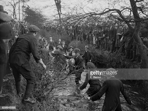 Players tussling for the ball in the brook during the Royal Shrovetide Football Match Ashbourne Derbyshire 7th February 1926 The game is played...
