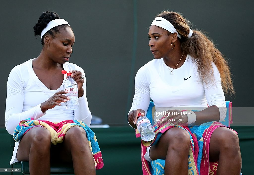 US players Venus Williams (L) and Serena Williams rest between sets their women's doubles second first round match against Georgia's Oksana Kalashnikova and Ukraine's Olga Savchuk on day three of the 2014 Wimbledon Championships at The All England Tennis Club in Wimbledon, southwest London, on June 25, 2014.