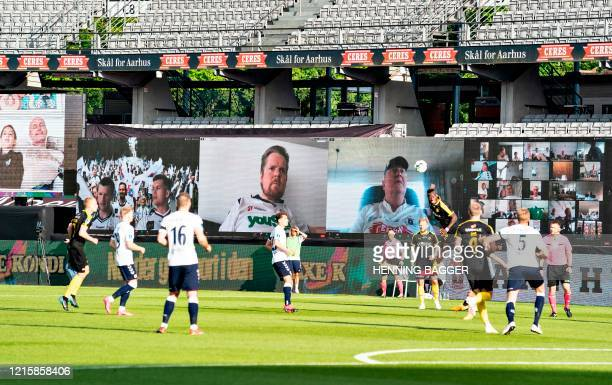 Players vie for the ball as fans are streamed live on to the screens on the sidelines during the 3F Super League football match between AGF and...