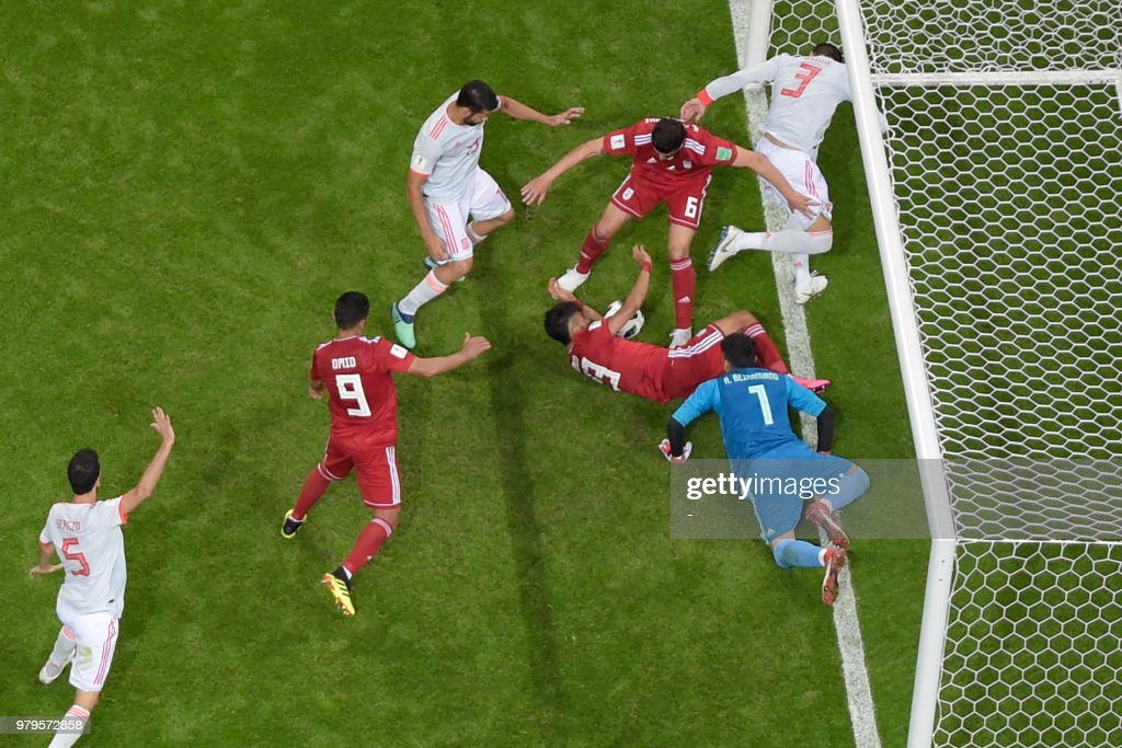 TOPSHOT - Players vie for the loose ball during the Russia 2018 World Cup Group B football match between Iran and Spain at the Kazan Arena in Kazan on June 20, 2018. (Photo by - / AFP) / RESTRICTED