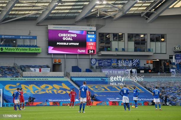 Players wait as a screen displays VAR checking for a goal during the English Premier League football match between Brighton and Hove Albion and...
