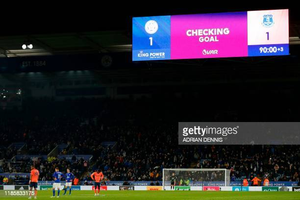 Players wait as the scoreboard shows that the VAR is checking the goal shortly before deciding Leicester City's Nigerian striker Kelechi Iheanacho...
