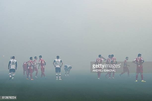 Players wait for the smoke disperses from the pitch after supporters burnt torches during the Serbian National soccer league derby match between...