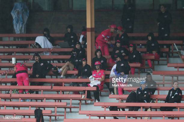 Players wait in the stands during a rain delay during the Women's Big Bash League WBBL match between the Sydney Sixers and the Adelaide Strikers at...