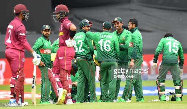 Players wait to resume play after the dismissal of West Indies' Nicholas Pooran during the 2019 Cricket World Cup group stage match between West...
