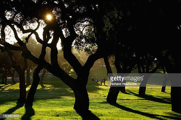 Players walk down the 1st fairway as the early morning sun filters through the cork trees during the second round of the Andalucia Masters at...
