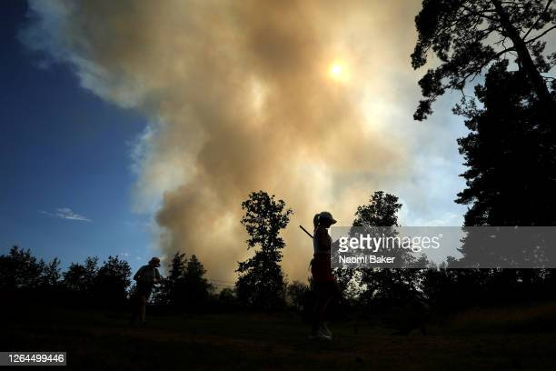 Players walk on the 10th hole as large fire and smoke is seen in near by Chobham Common during day three of The Rose Ladies Series on The West Course...