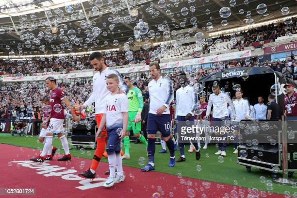 Players walk onto the pitch prior to the Premier League match between West Ham United and Tottenham Hotspur at London Stadium on October 20 2018 in...