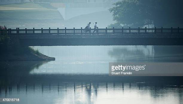 Players walk over a bridge during the second round of the Shenzhen International at Genzon Golf Club on April 17 2015 in Shenzhen China