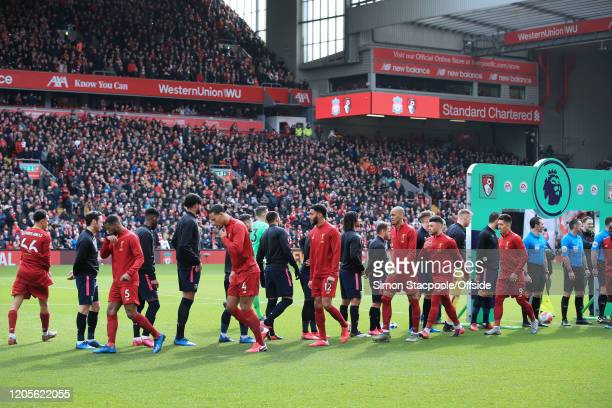 Players walk past eachother without shaking hands due to Coronavirus concerns before the Premier League match between Liverpool FC and AFC...
