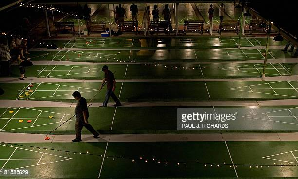 Players walk to the opposite end of the court at the St Petersburg Shuffleboard Club during evening community games May 23 in St Petersburg Florida...