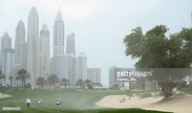 Players walk up the eighth fairway as strong wind blows sand across the hole during the second round of the Omega Dubai Desert Classic on the Majils...