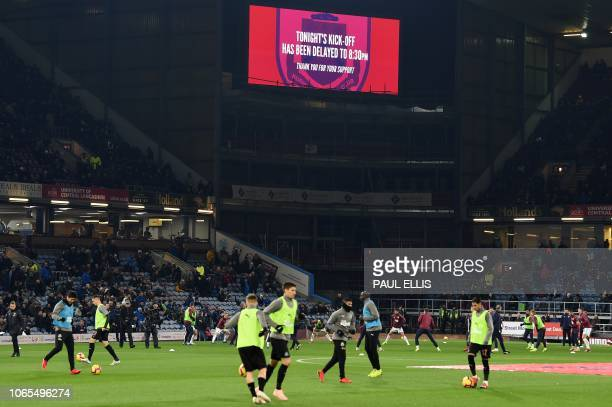 Players warm up beneath a screen announceing that the match has been delayed ahead of the English Premier League football match between Burnley and...