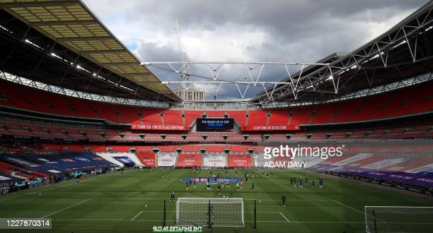 Players warm up in front of empty seats ahead of the English FA Cup final football match between Arsenal and Chelsea at Wembley Stadium in London, on...