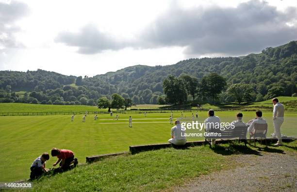 Players watch a game of village cricket from the boundary at Ambleside Cricket Club on July 26 2008 in Ambleside England