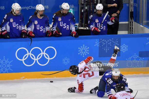 US players watch as Canada's Sarah Nurse falls in front of USA's Amanda Kessel in the women's gold medal ice hockey match between the US and Canada...