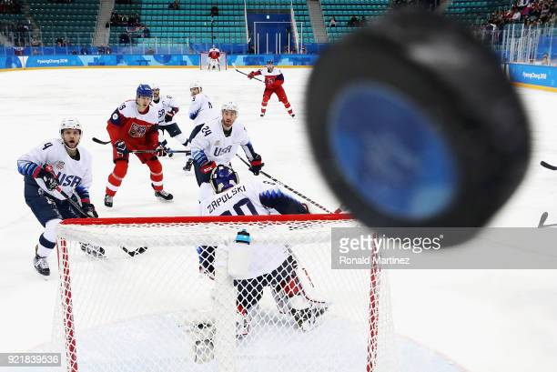 Players watch as the puck hits the glass in the first period of the Men's Play-offs Quarterfinals between the Czech Republic and the United States on...
