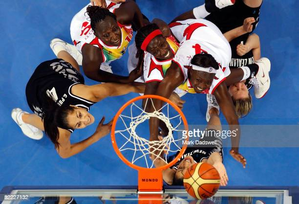 Players watch the ball as a basket is scored during the women's preliminary basketball game between New Zealand and Mali played at the Beijing...