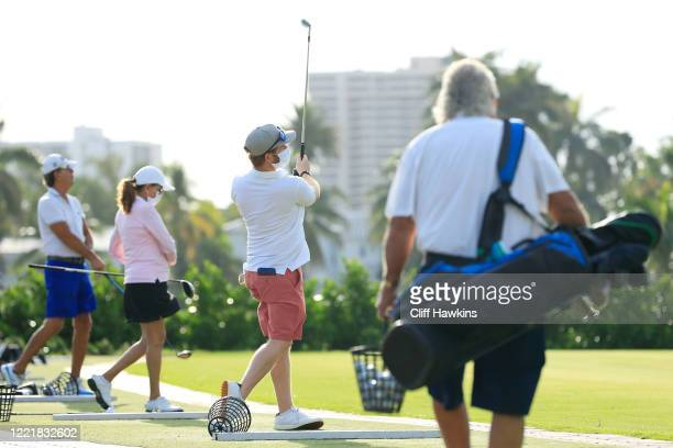 Players wearing face masks warm up on the range at the Miami Beach Golf Club on April 29 2020 in Miami Beach Florida The city of Miami Beach...