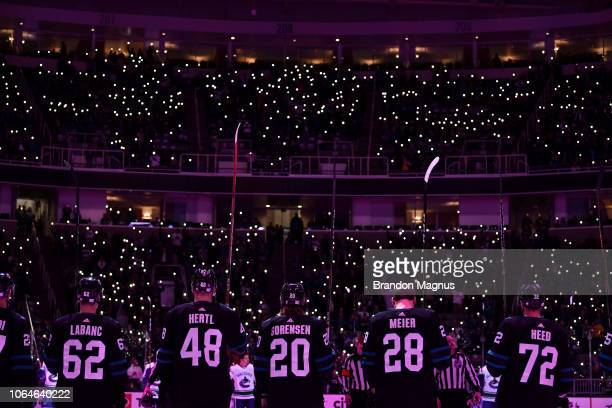 Players with their sticks raised and fans join in a moment of silence before the San Jose Sharks and Vancouver Canucks game at SAP Center on November...