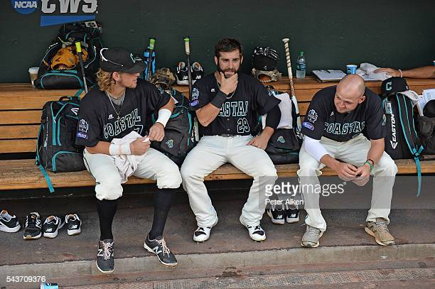 Players Zach Remillard Anthony Marks and Mike Morrison of the Coastal Carolina Chanticleers set in the dugout while game three of the College World...
